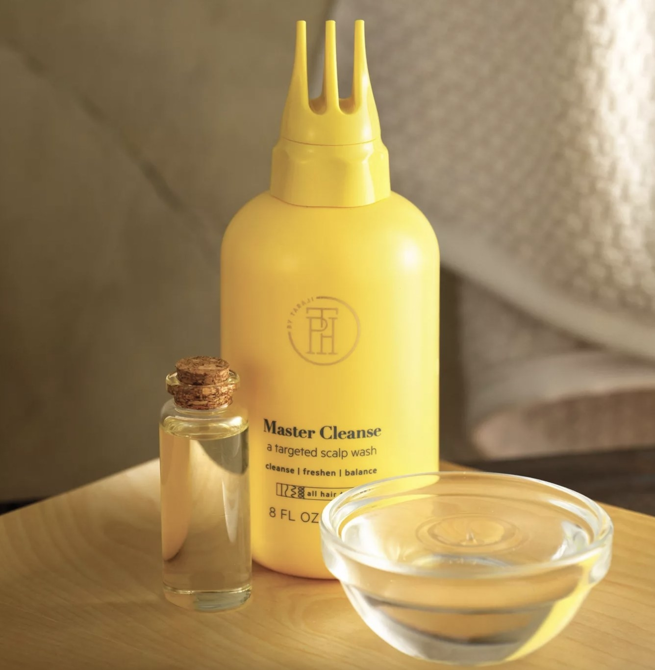 A bottle of scalp treatment with a small bottle of oil and a clear bowl