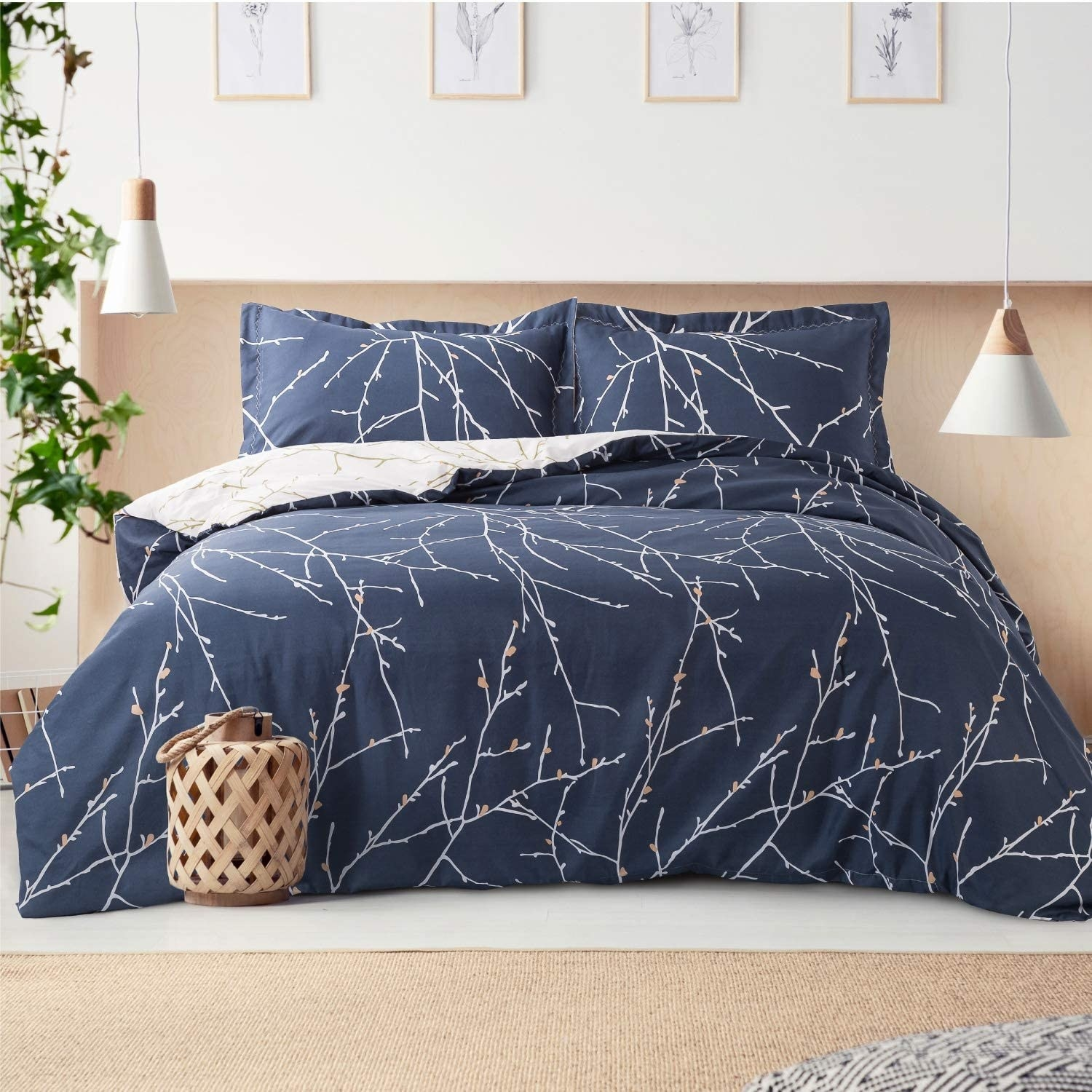 the navy blue bed set with white tree branches all over it on a bed