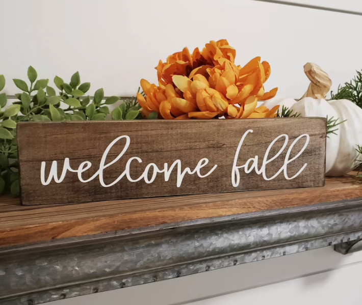 """A wooden sign that reads """"welcome fall"""" in white cursive font"""