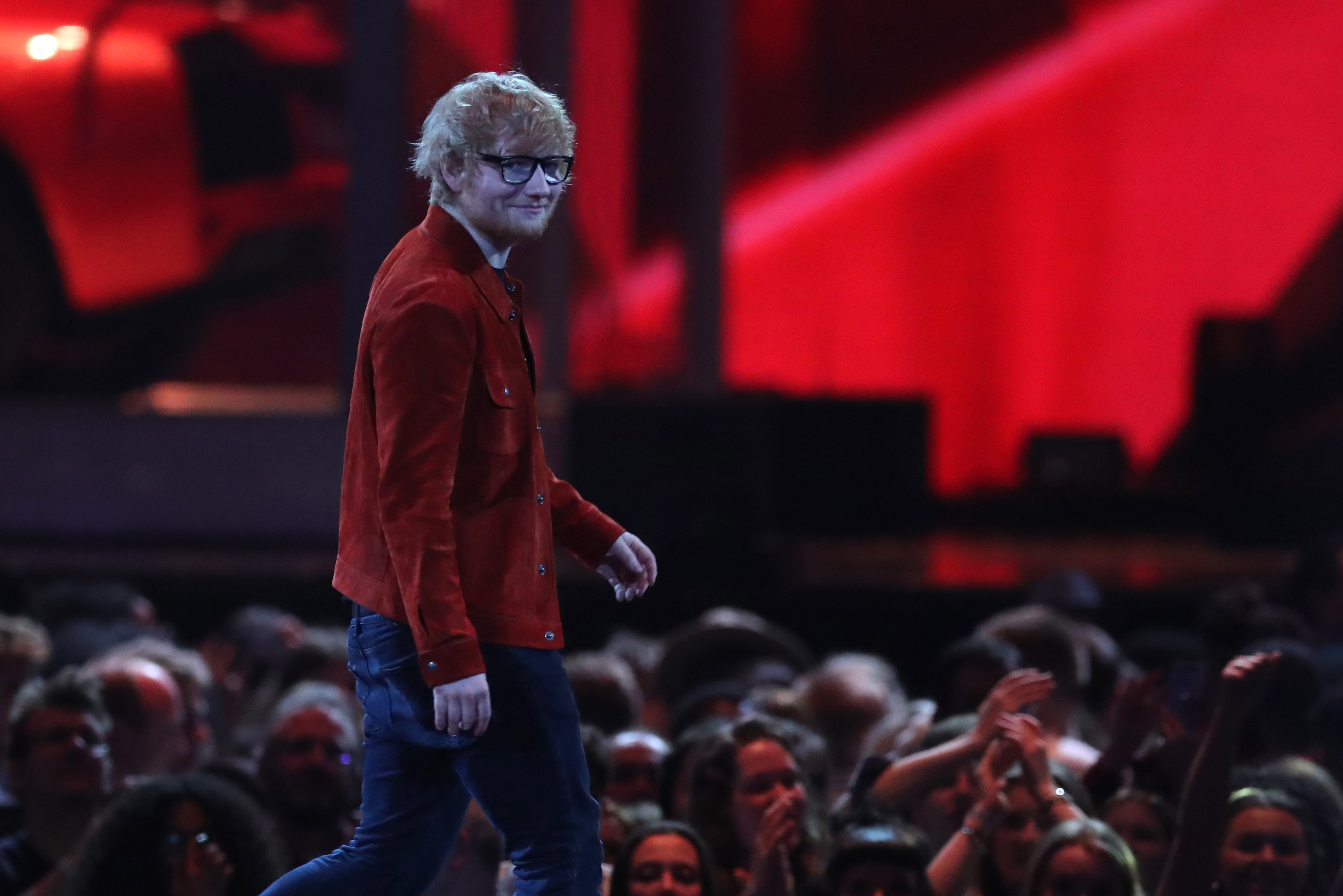 Ed walks across a stage in a front of an audience at an award show