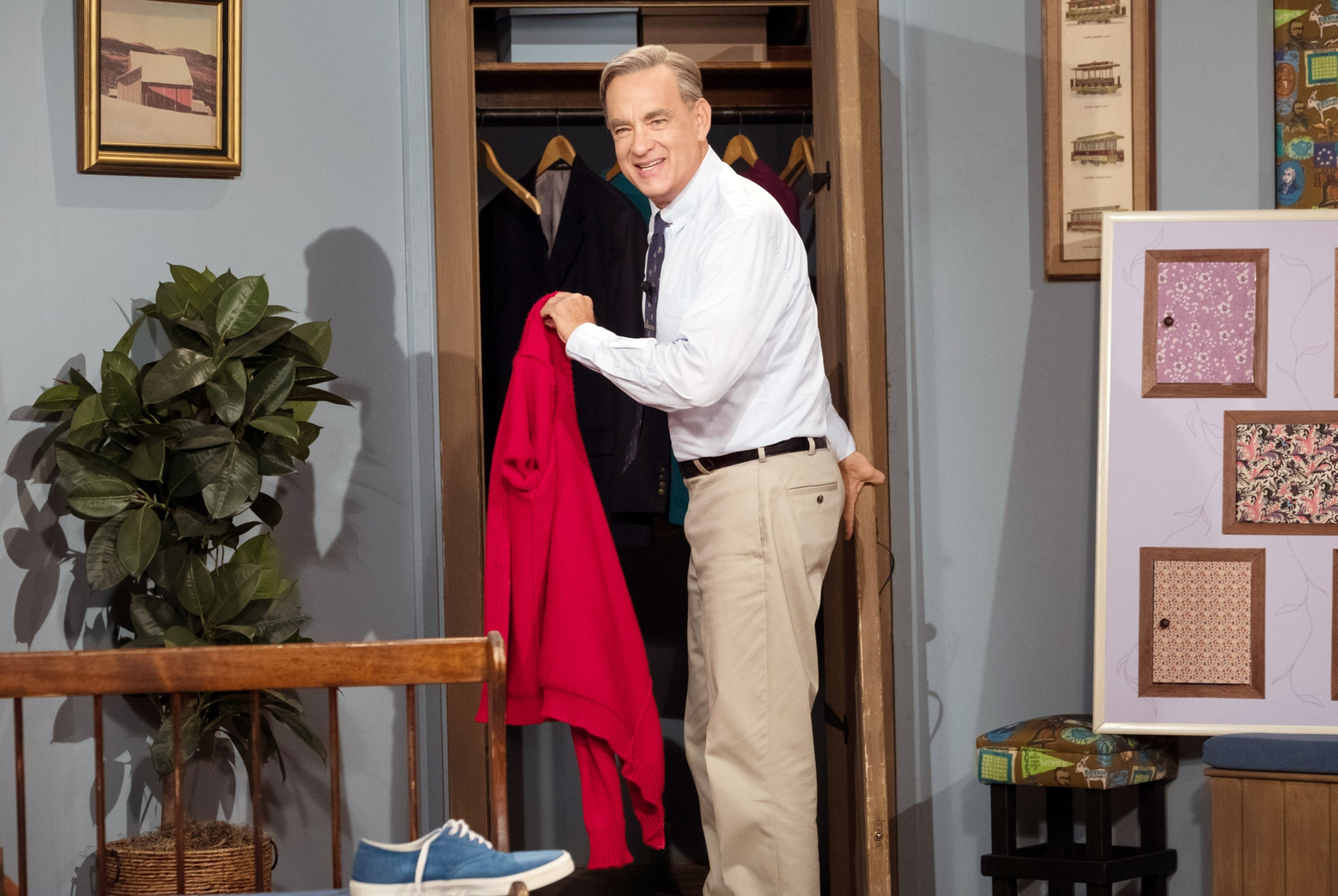 Fred Rogers dressed in sneakers, pants, a shirt and tie, and holding a sweater in the film