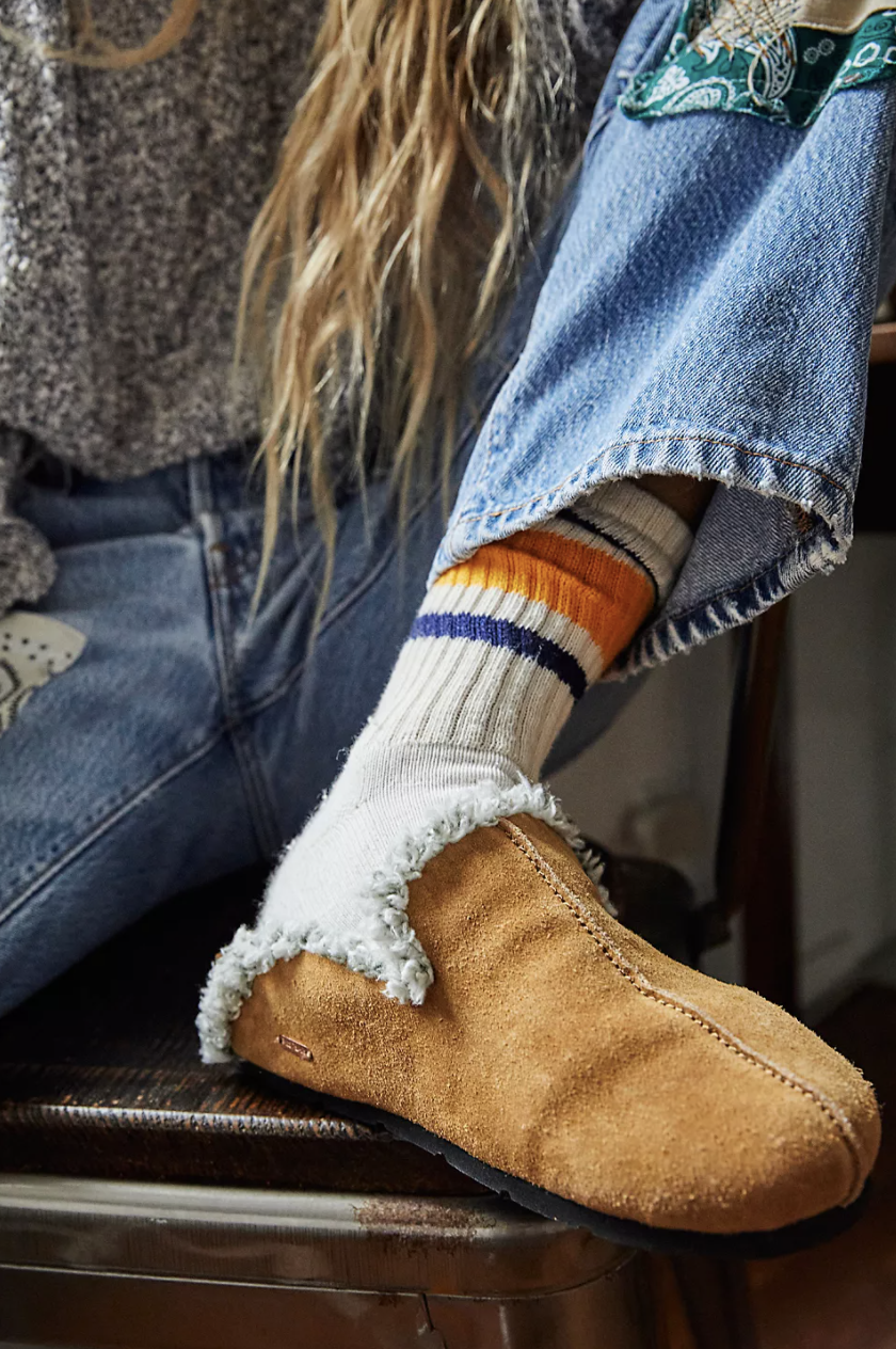 closeup of model wearing a slip on leather mule with socks