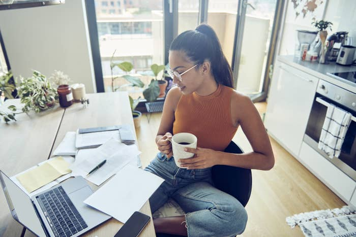 Woman looking at her finances with a laptop and phone