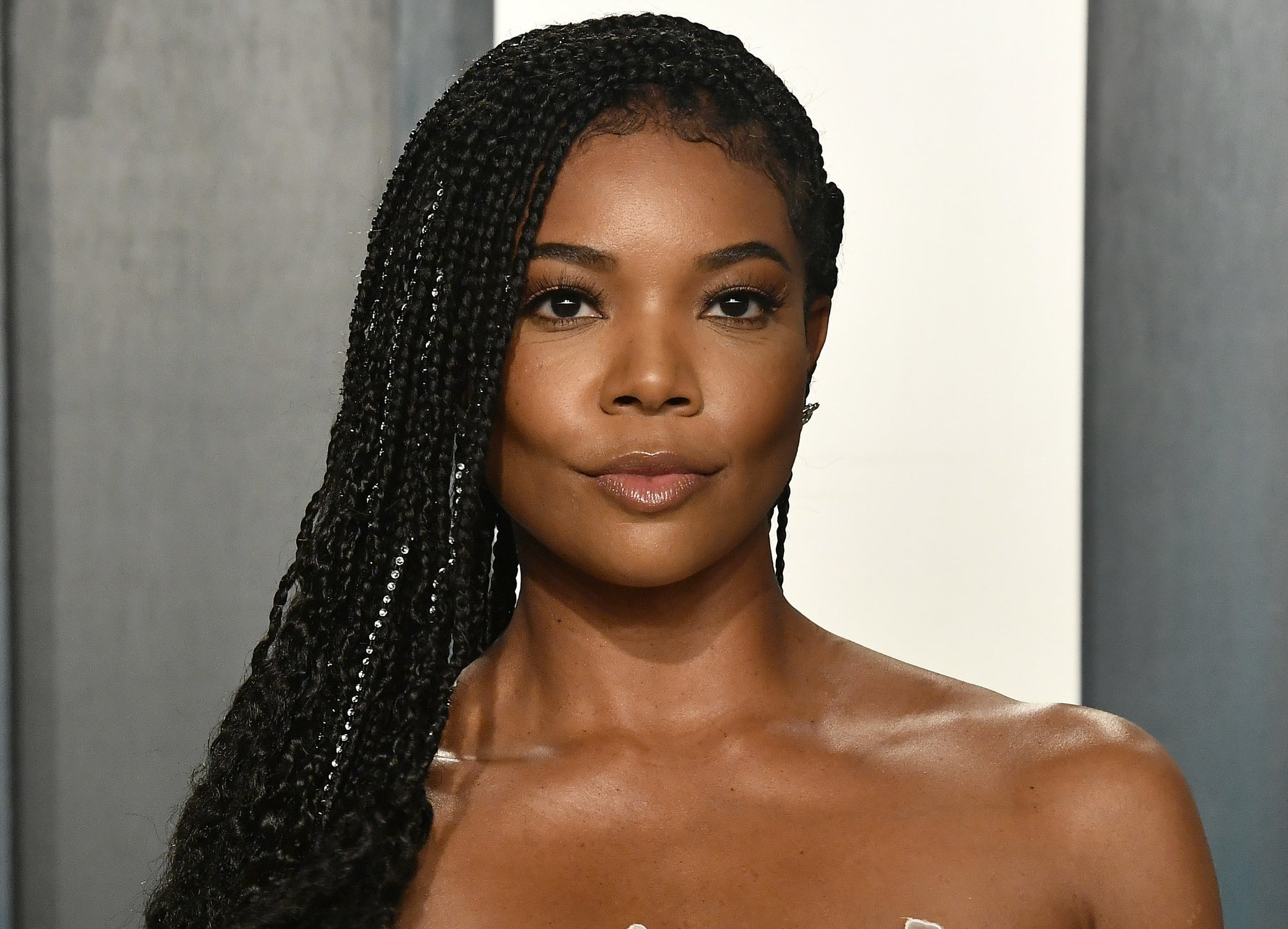 A close up of Gabrielle at an event with her braided hair pushed to one side