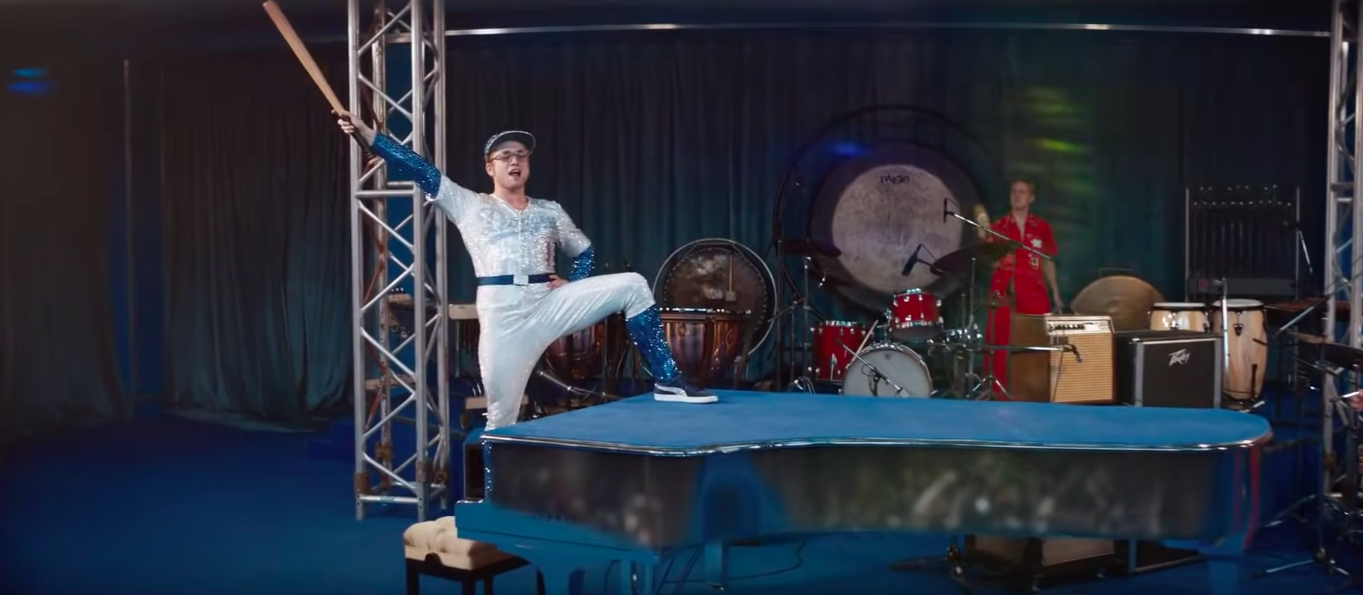 Elton John performing while wearing a jeweled baseball outfit in the film