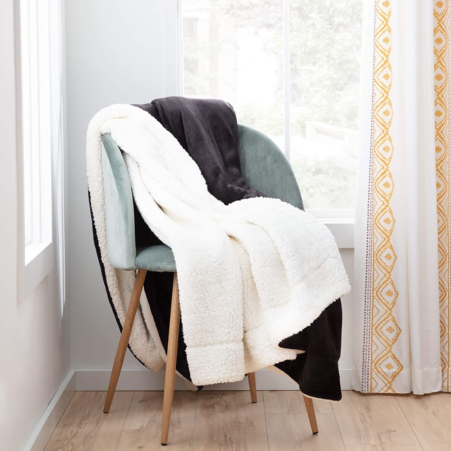 The blanket, which has a dark gray fleece side and a white sherpa side, lying on a chair