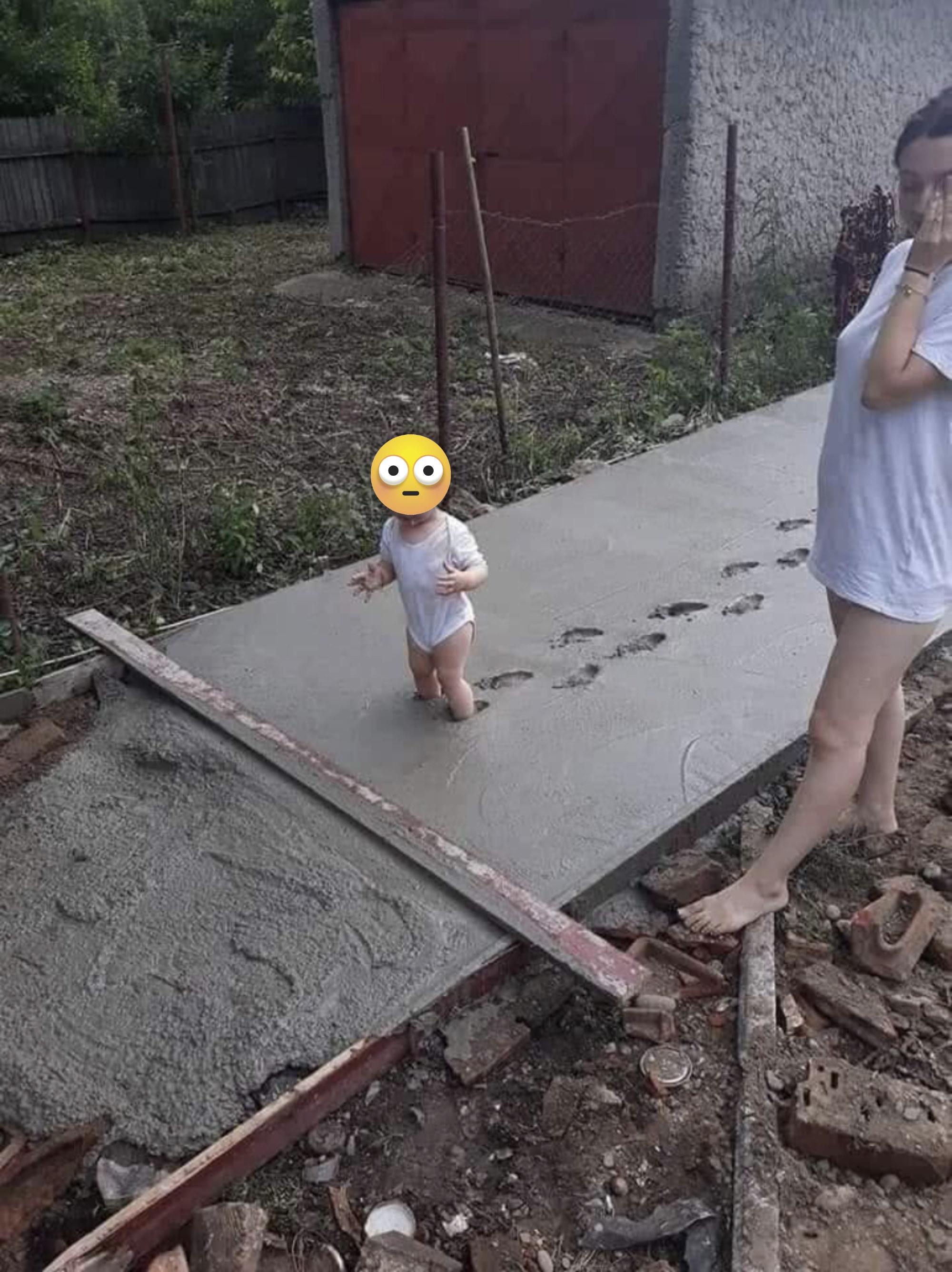 A baby walks in wet cement