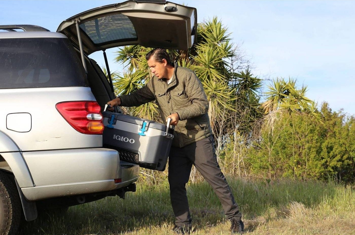 man putting ice chest into the trunk of a car
