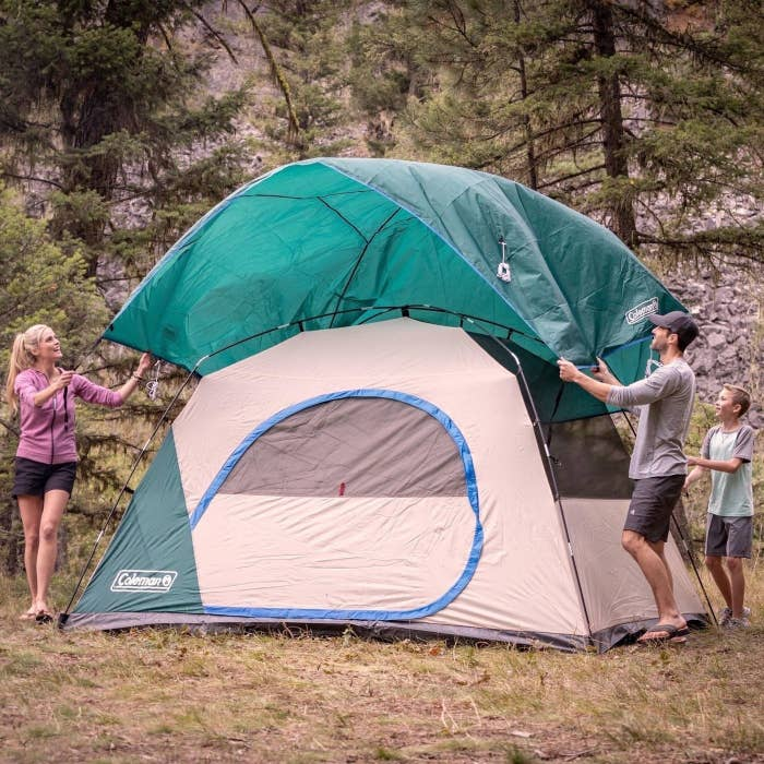 a family setting up the green tent outside