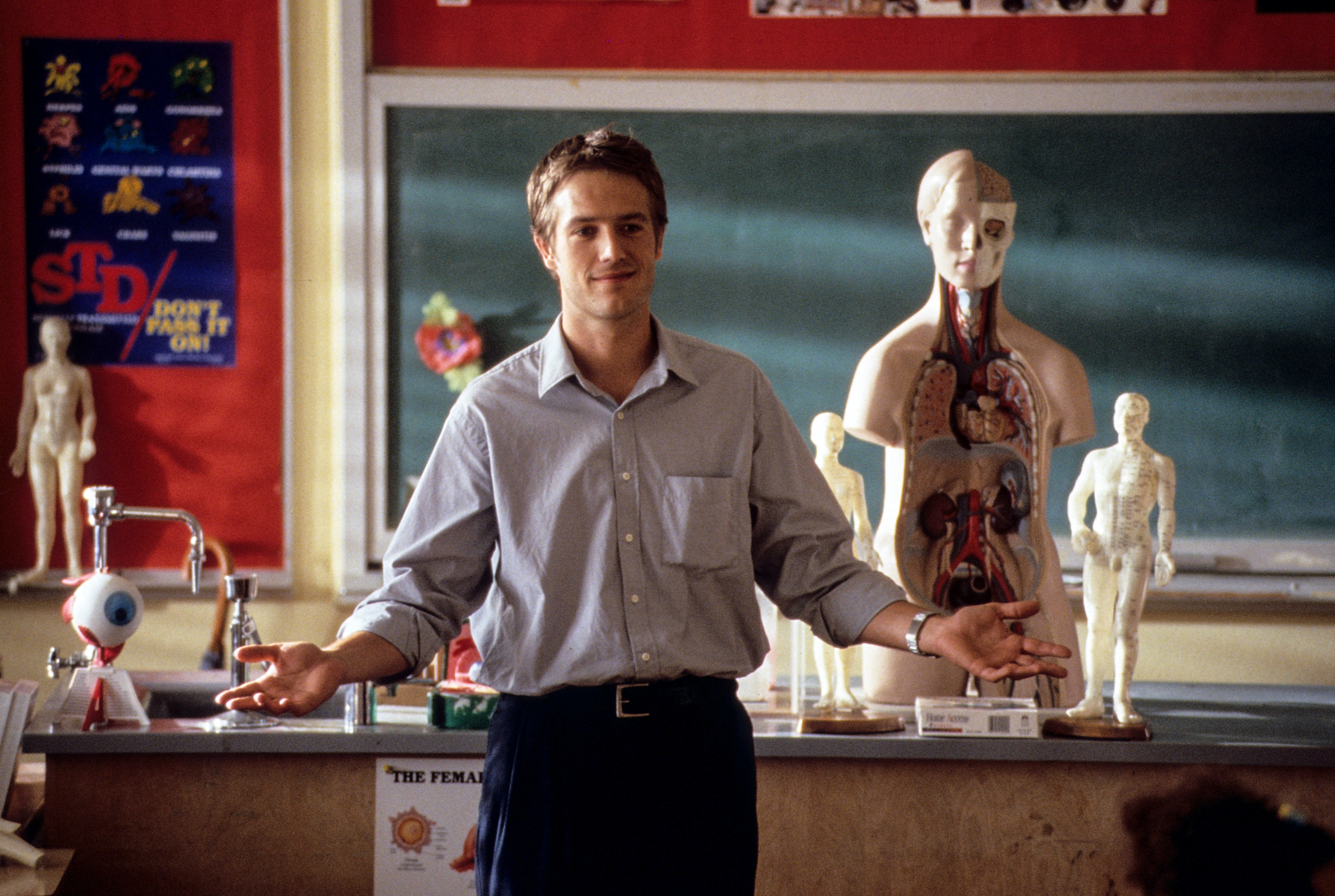 Michael's character stands in front of a classroom while teaching