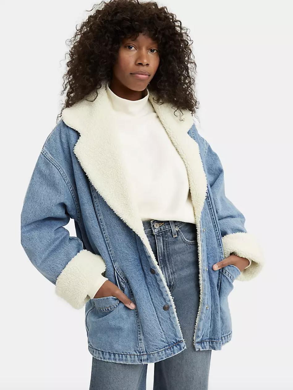 model wearing retro-inspired denim jacket with sherpa lining