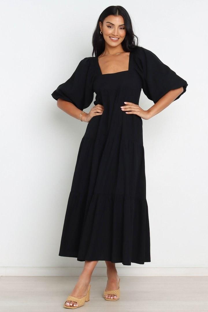model in long sleeve midi length black dress