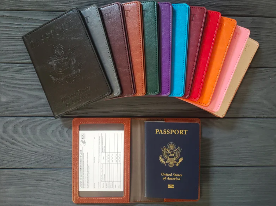 An image of a variety of the vaccine passports in multiple colors with one of them open showing where your passport and vaccination card fit