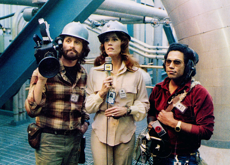 Jane Fonda stands with a mic between Michael Douglas and Daniel Valdez, her crew
