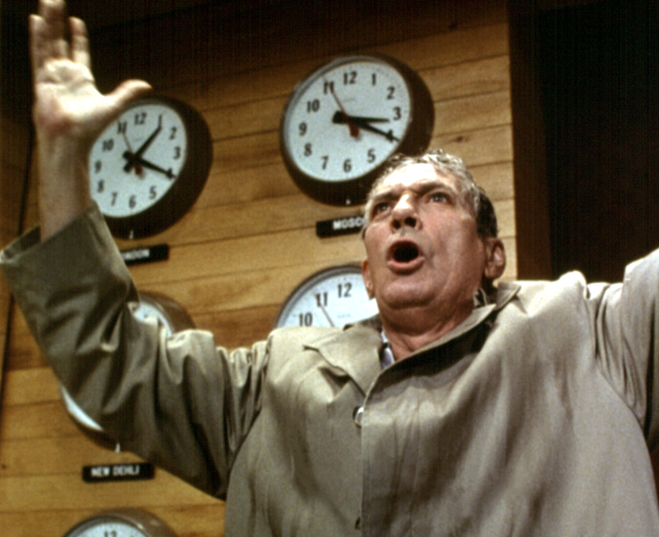 Peter Finch shouts in front of a wall of clocks drenched in a trench coat