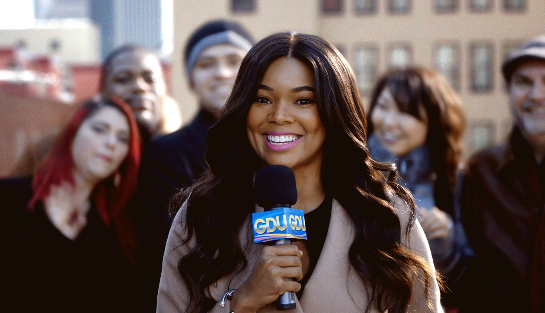 Gabrielle Union stands with a microphone with people behind her