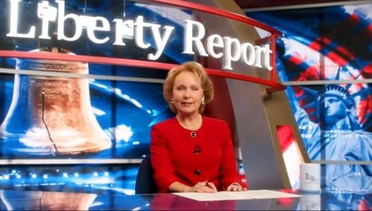 Kate Burton sits at a news desk