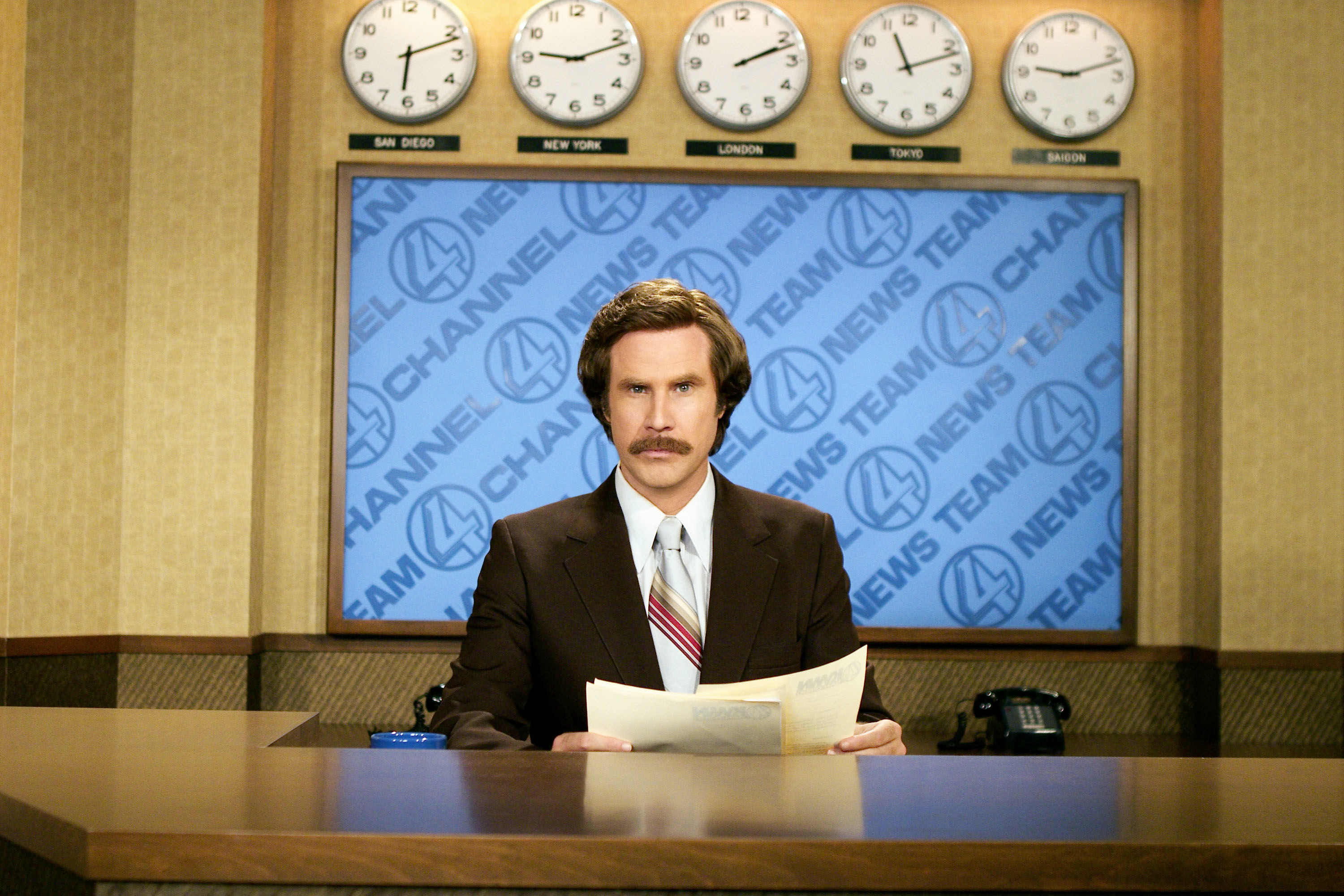 Will Ferrell sits with papers behind a news desk