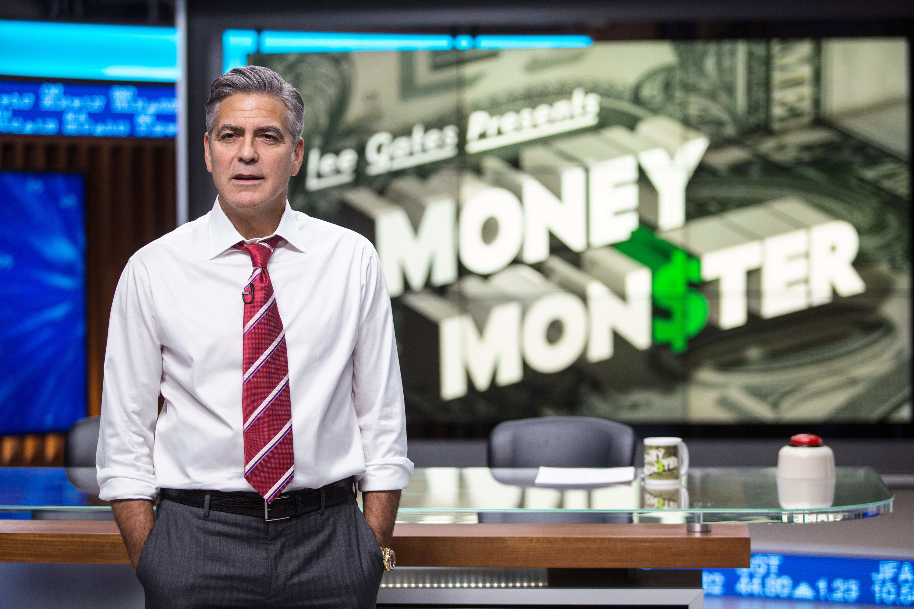 George Clooney stands in front of his news desk