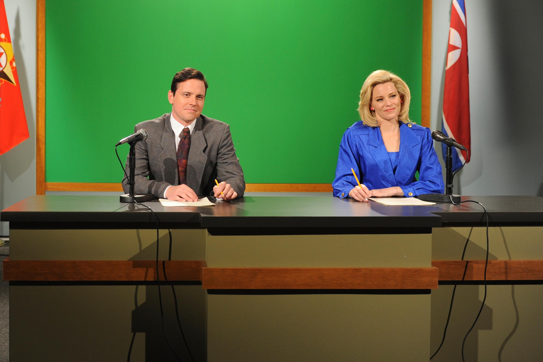 Michael Mosley and Elizabeth Banks sit behind a news desk