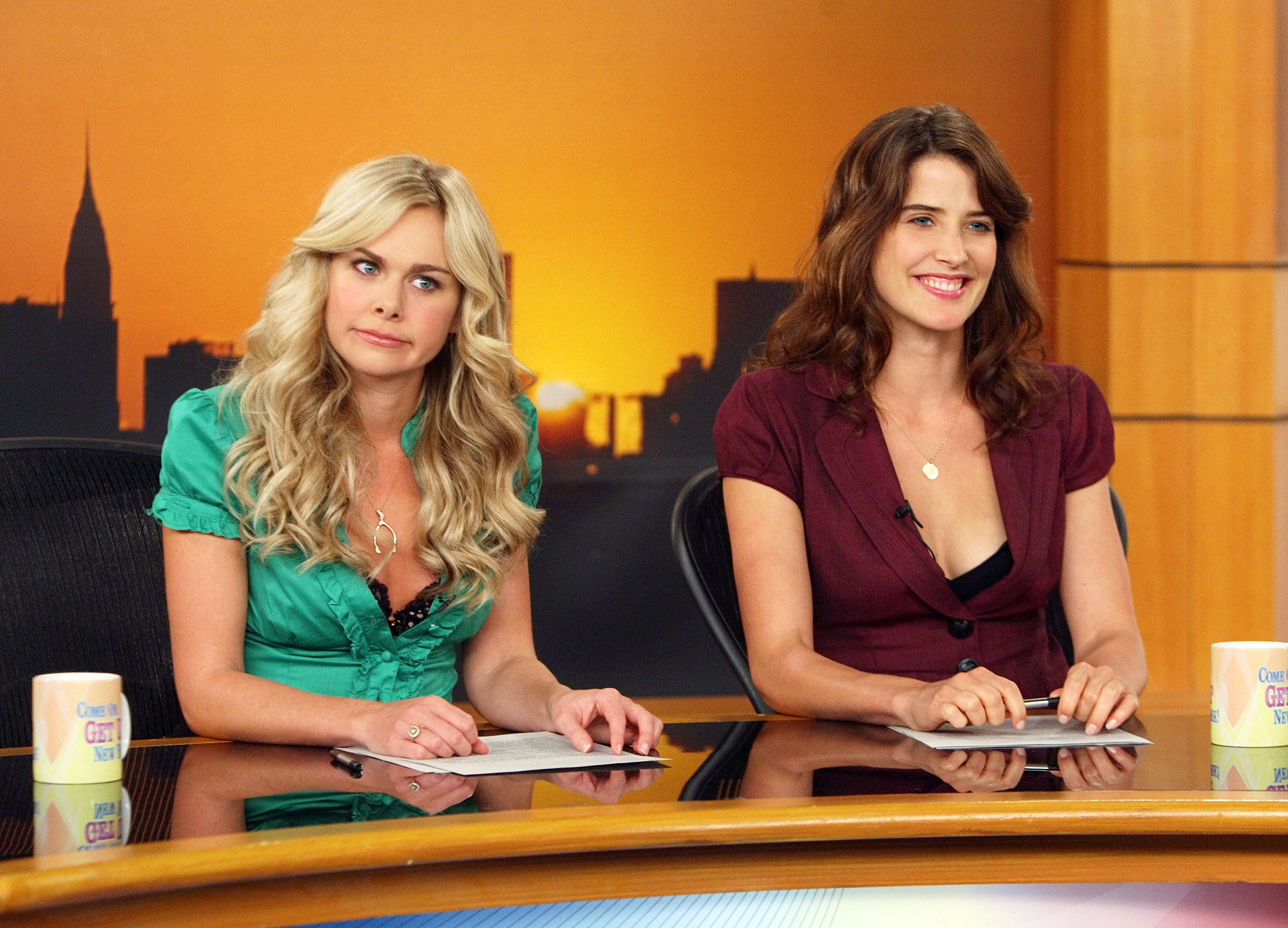 Laura Bell Bundy and Cobie Smulders sit behind a news desk