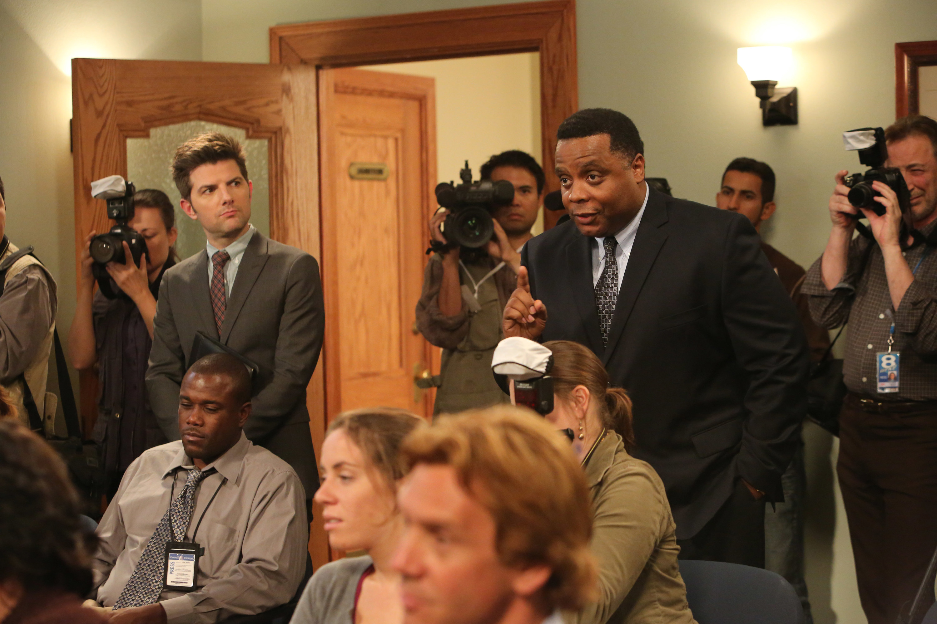 Adam Scott and Jay Jackson stand in the back of a press conference