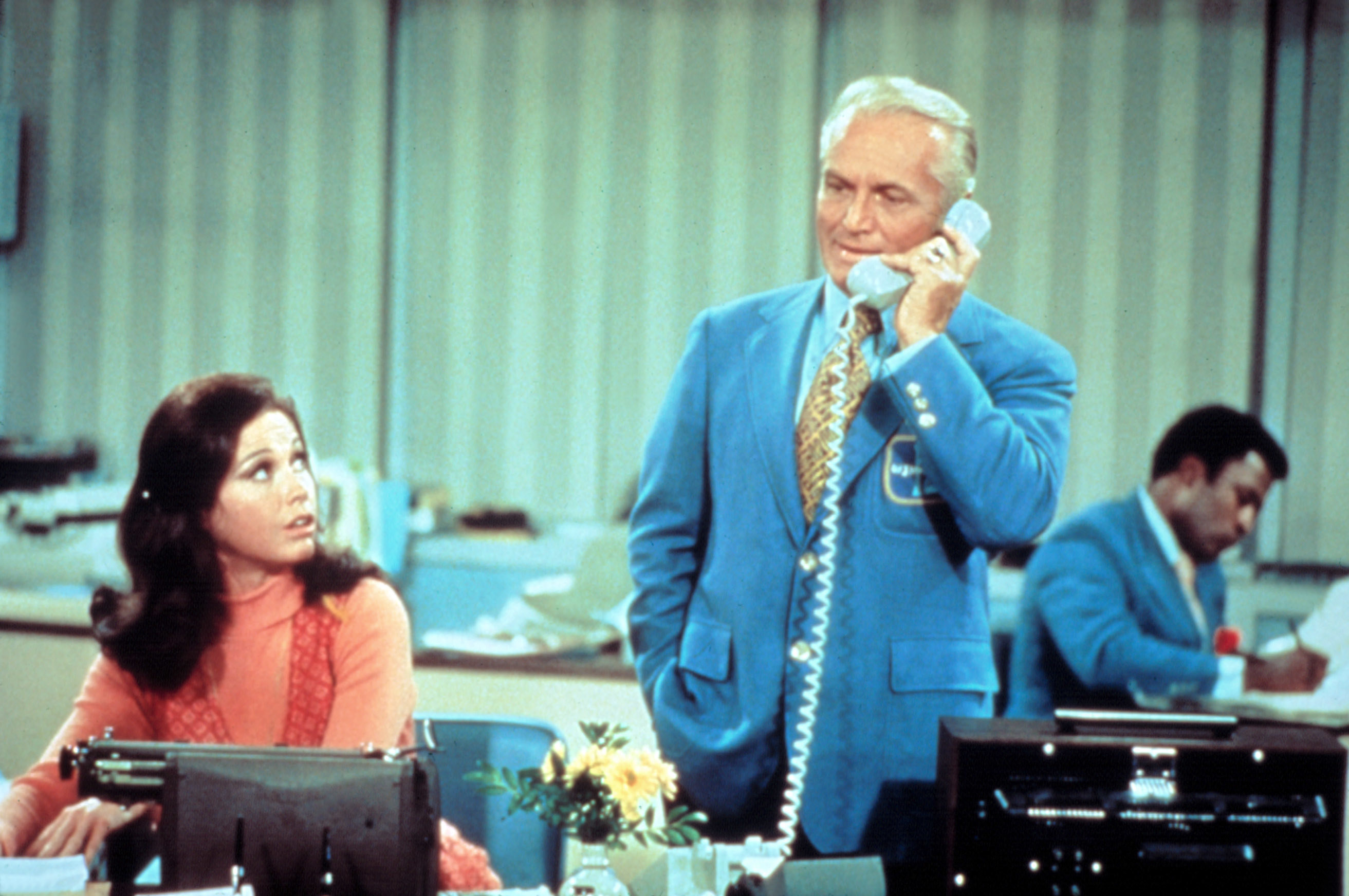 Mary Tyler Moore sits beside Ted Knight who is on the phone