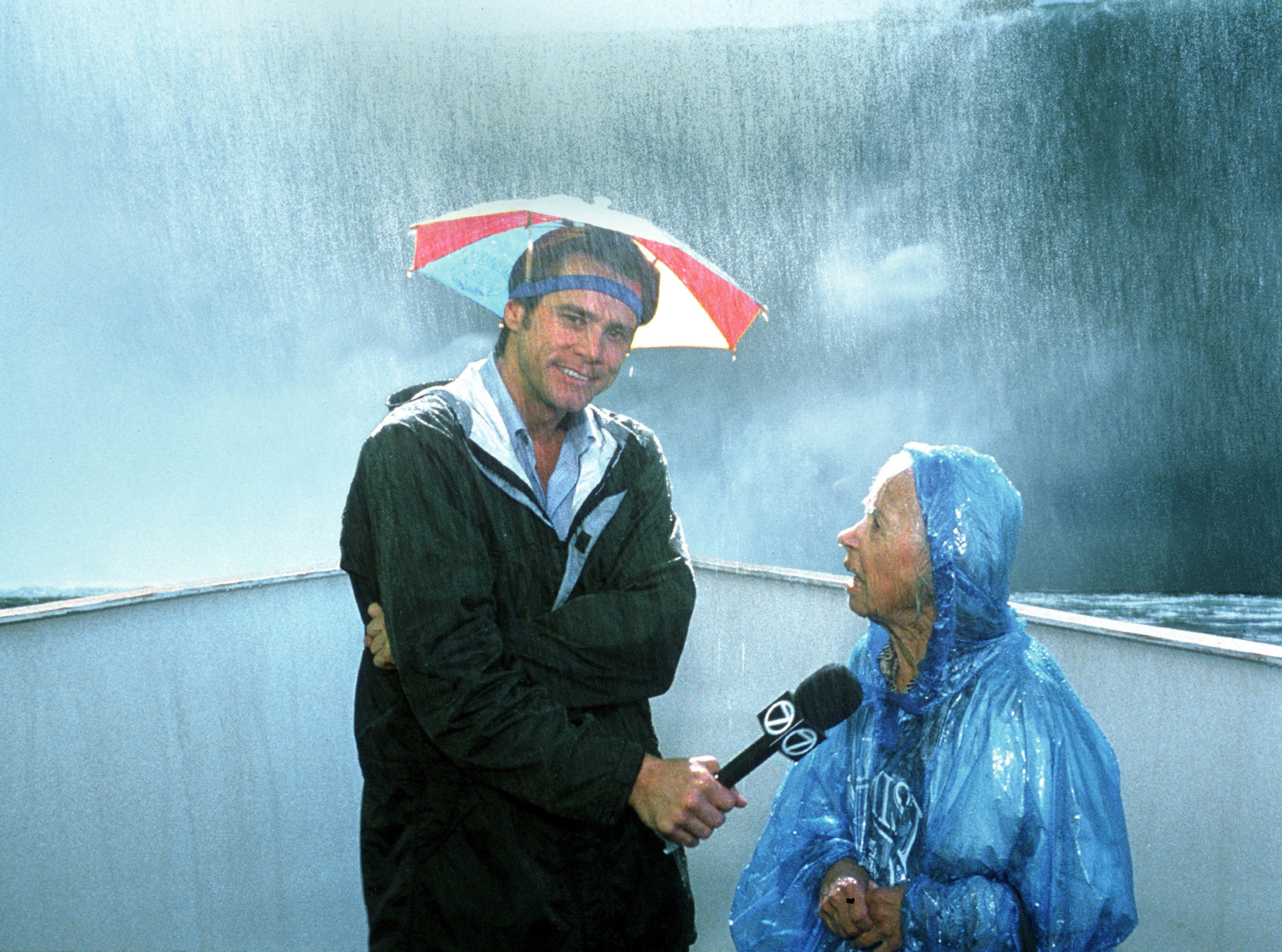 Jim Carrey interviews an older woman next to a waterfall
