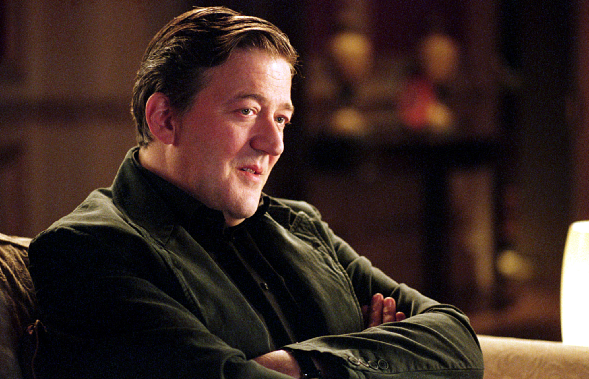Stephen Fry sits with his arms crossed