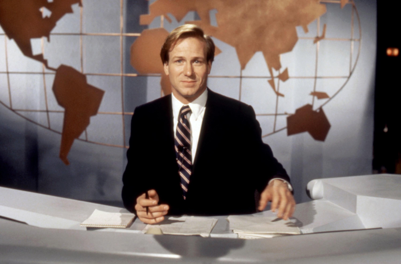 William Hurt sits behind a news desk