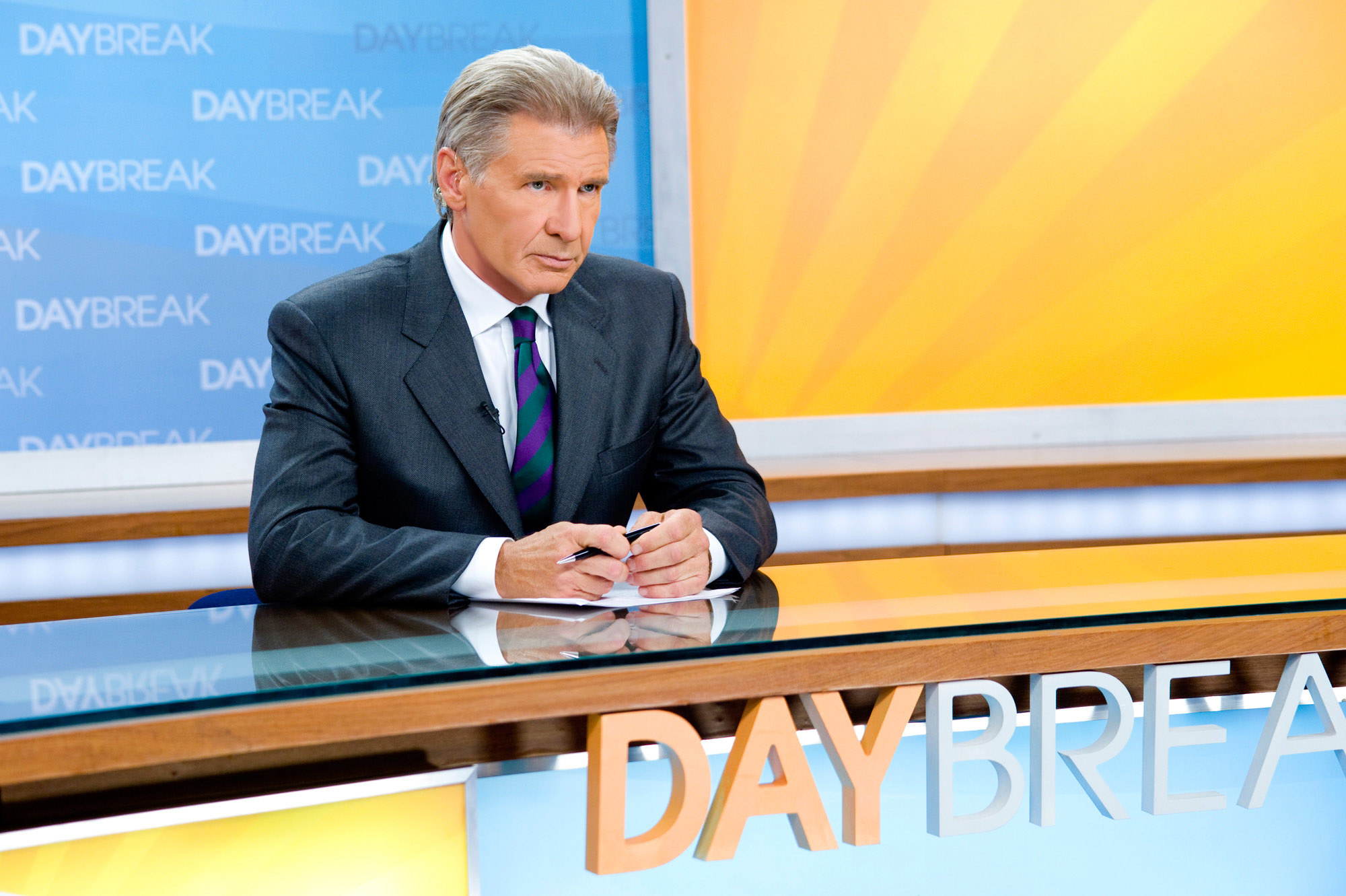 Harrison Ford sits behind a news desk