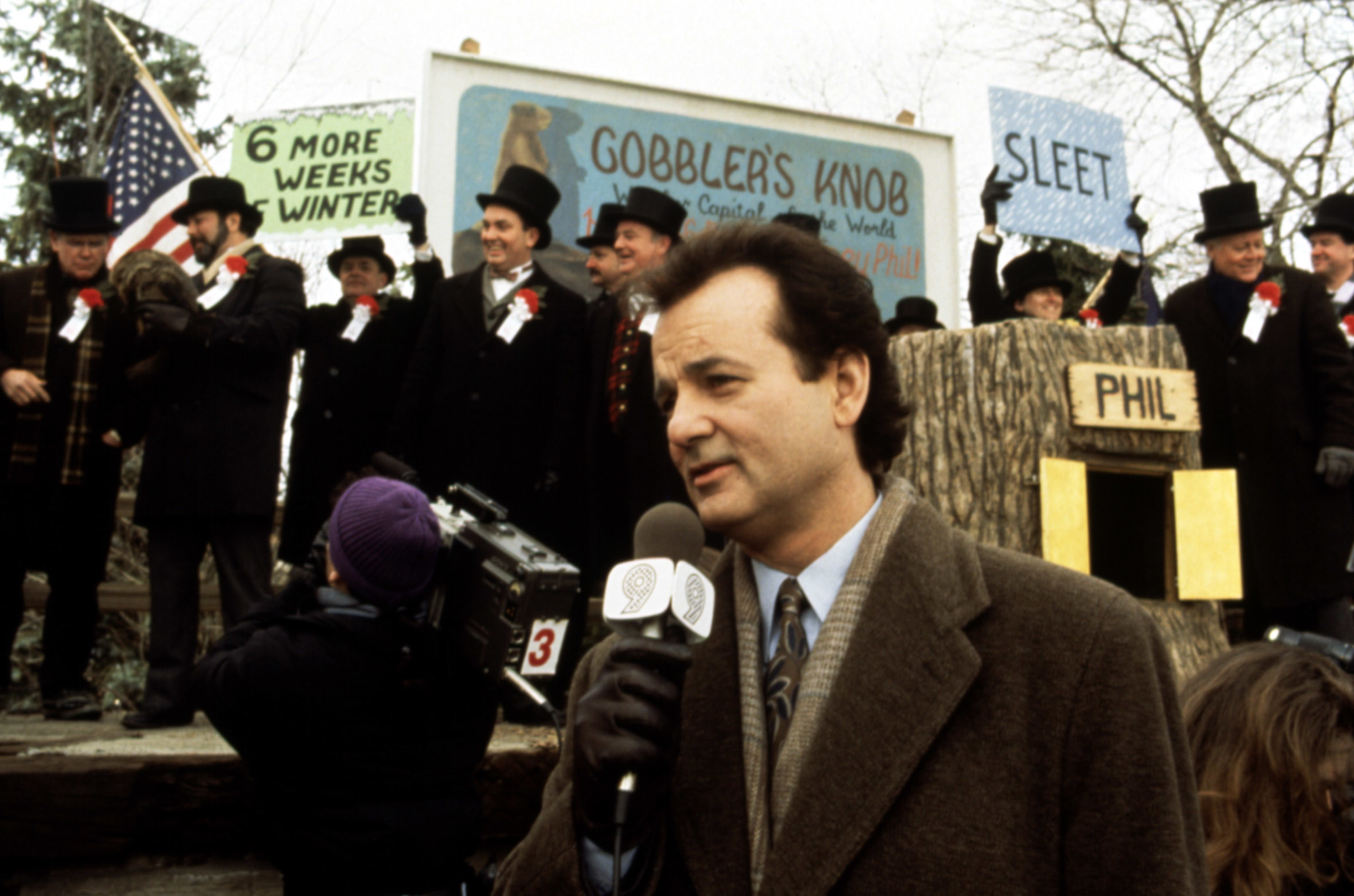 Bill Murray stands with a microphone in front of the groundhog stump