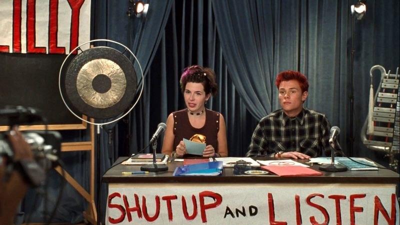 "Heather Matarazzo and Patrick Flueger sit behind the ""Shut Up and Listen"" desk"