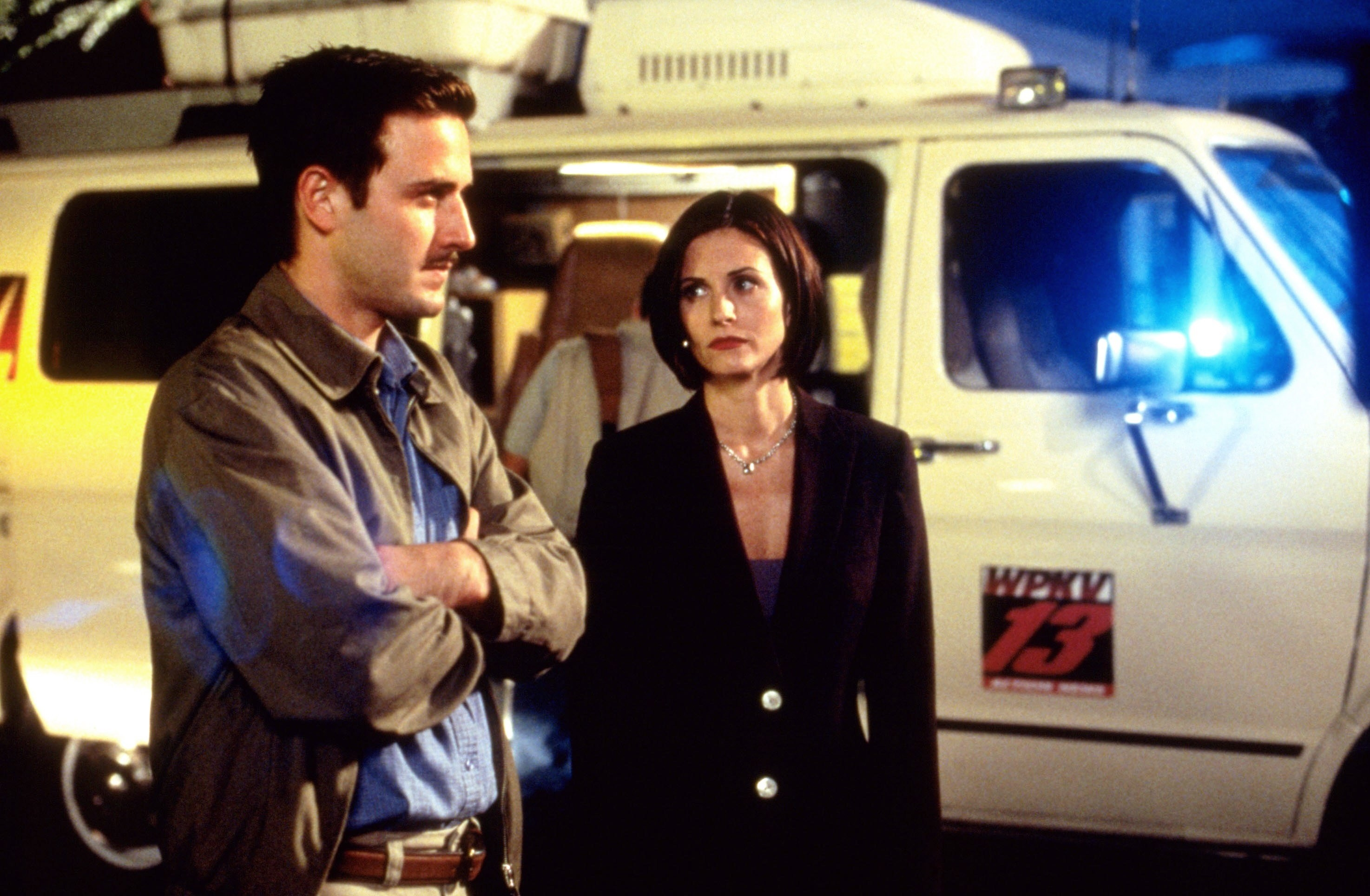 David Arquette andCourteney Cox stand in front of a news van
