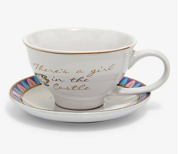 """a white tea cup with chip on it and """"there's a girl in the castle"""" written in gold on a saucer"""