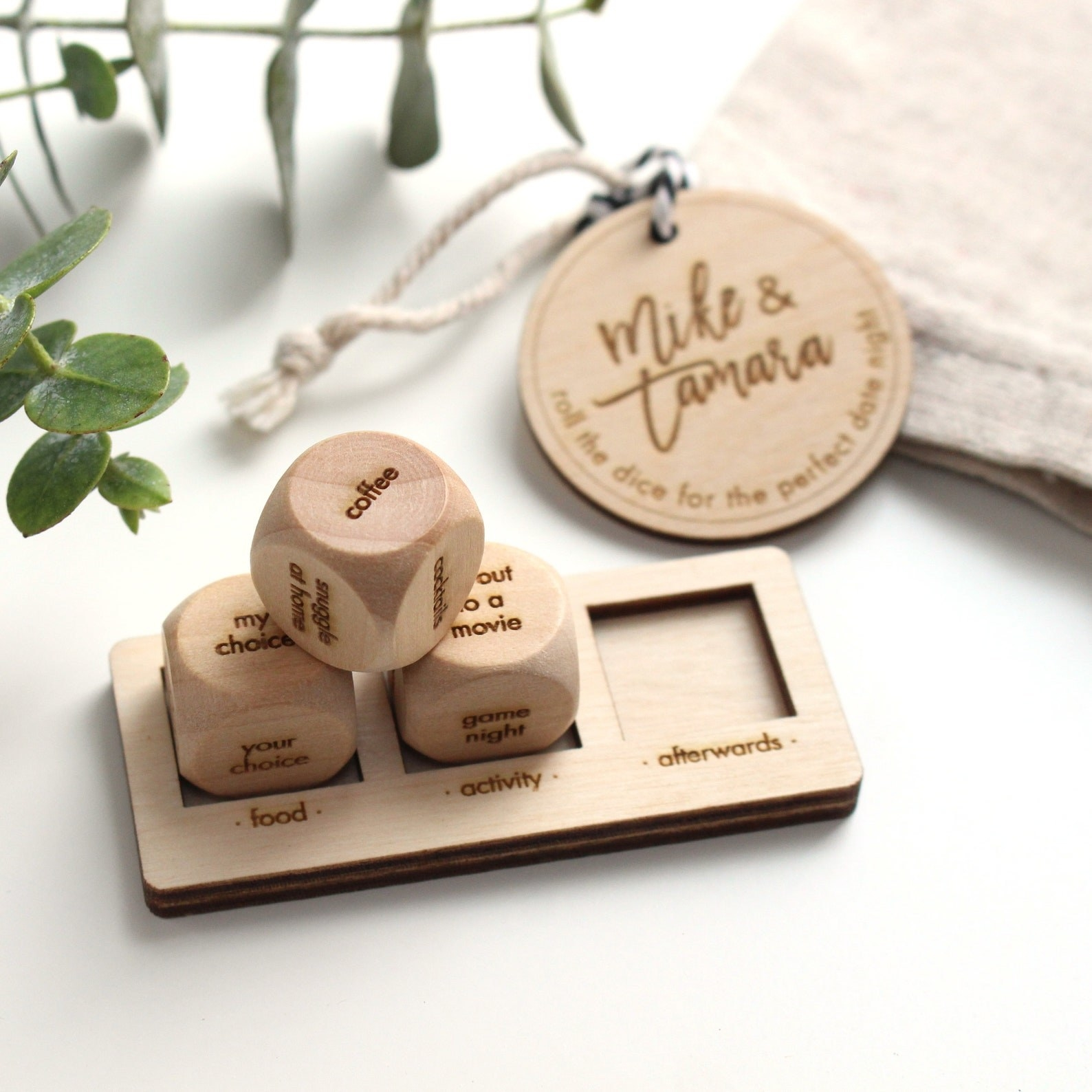 Three wooden dice engraved with activities resting on a mount with three spaces for food, activity, and afterwards