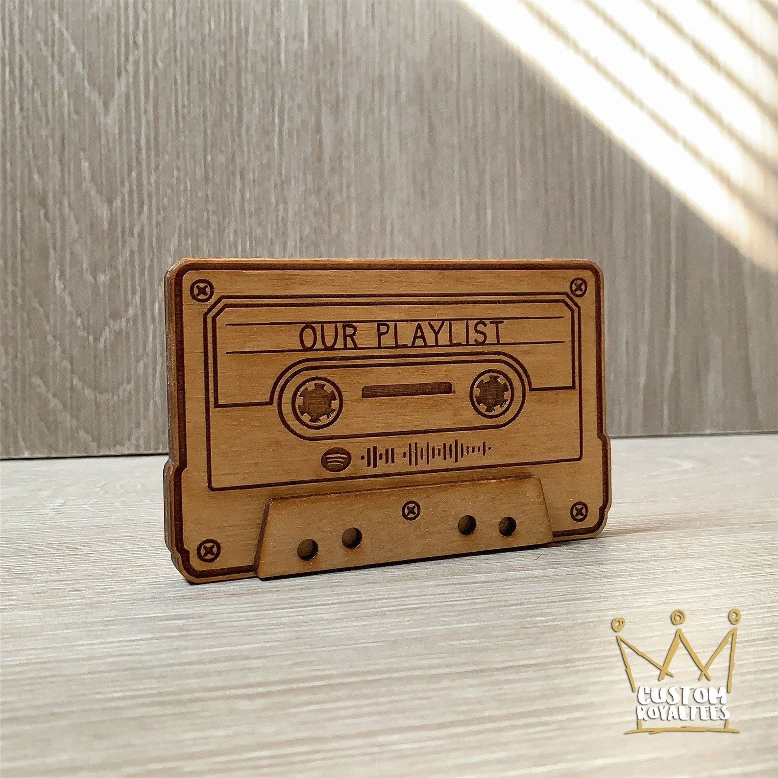 """An upright small wooden etched cassette that says """"Our Playlist"""" with a Spotify playlist code etched on it"""