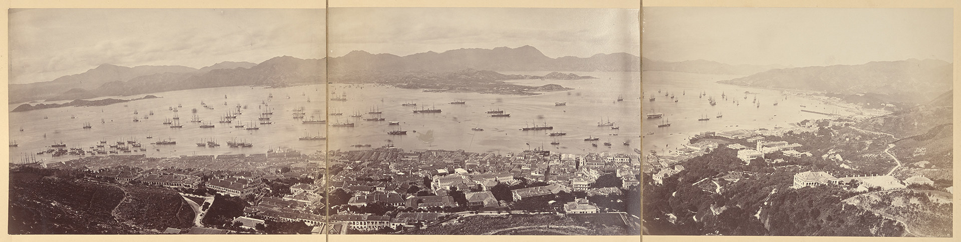 A panoramic view of Hong Kong Harbor, with several boats, ships, and other vessels on an expansive body of water, stitched together between three photos