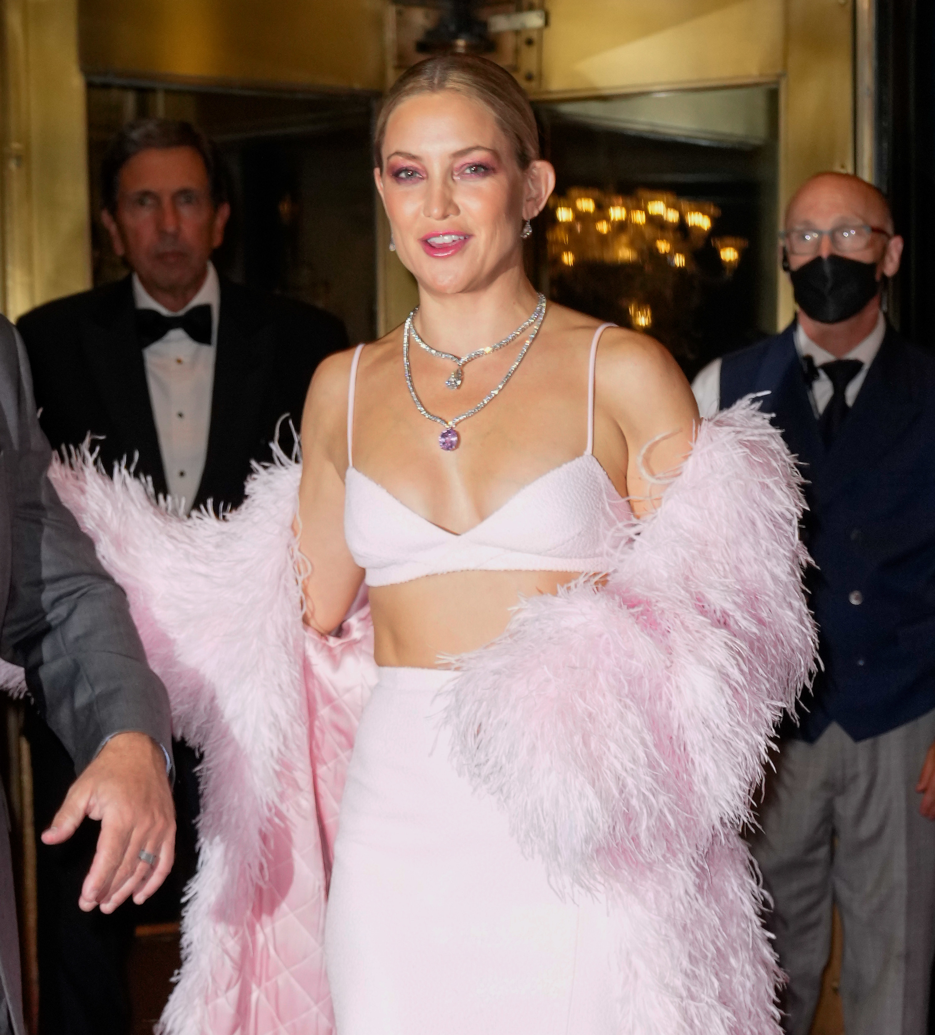 Kate walking at an event in a crop top, skirt, and matching feather jacket
