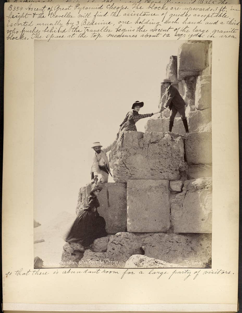 Four people climbing up the pyramids in Egypt