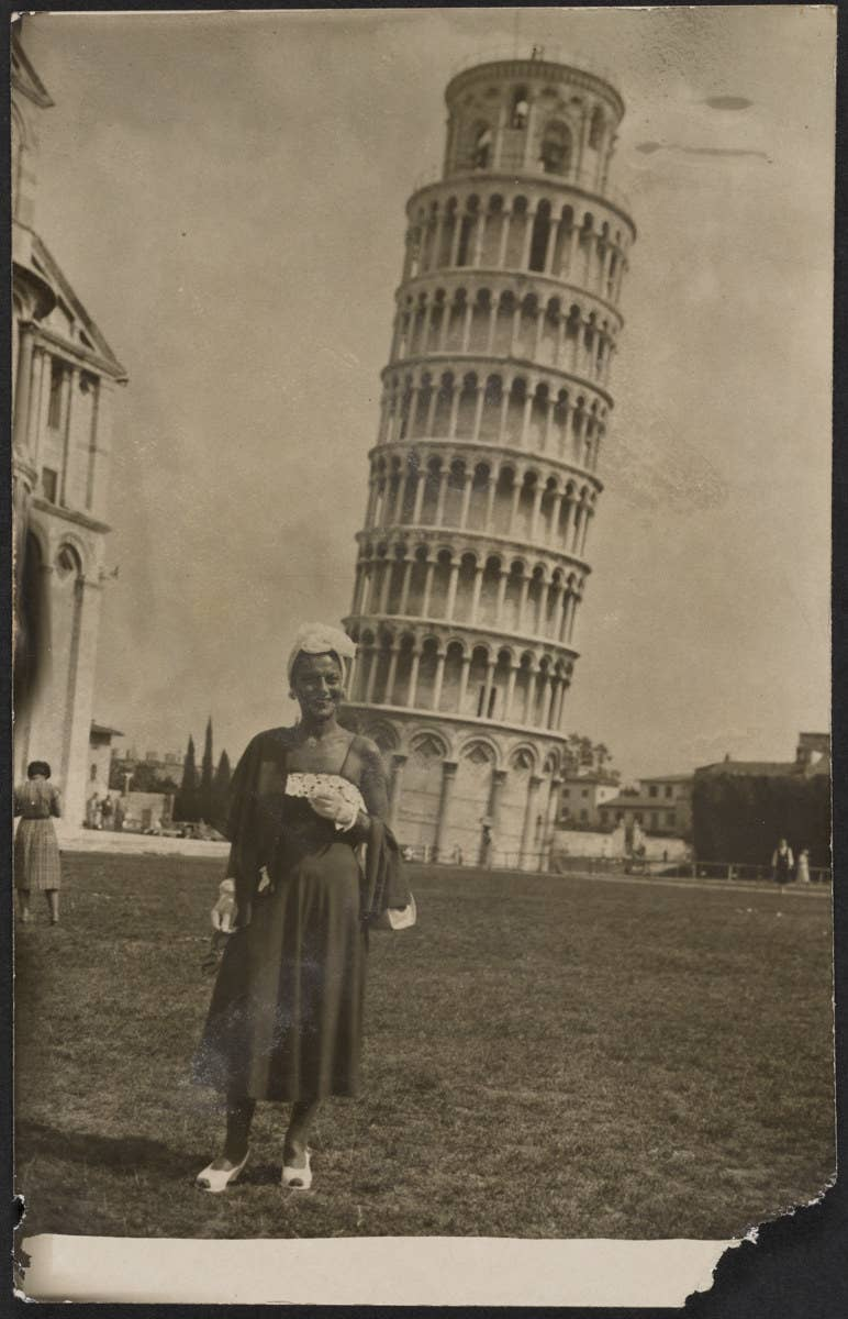 A woman wears a dress and floral headpiece in front of the Leaning Tower of Pisa in a midcentury photo