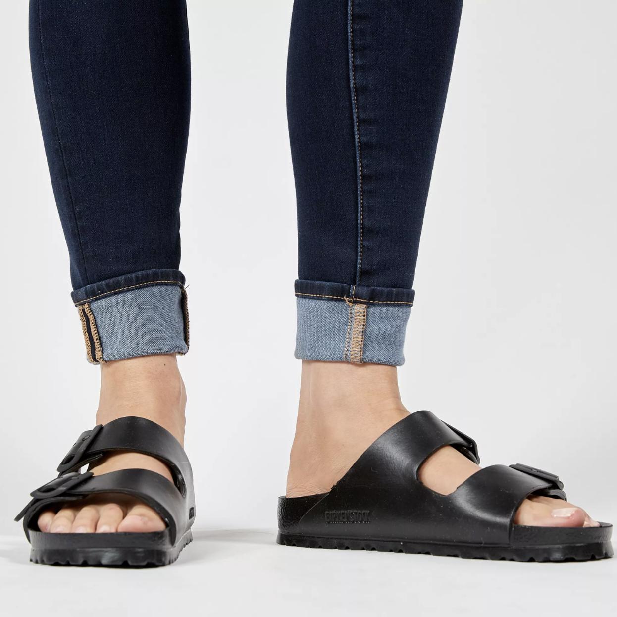 model wearing black waterproof birkenstocks with cuffed dark wash skinny jeans