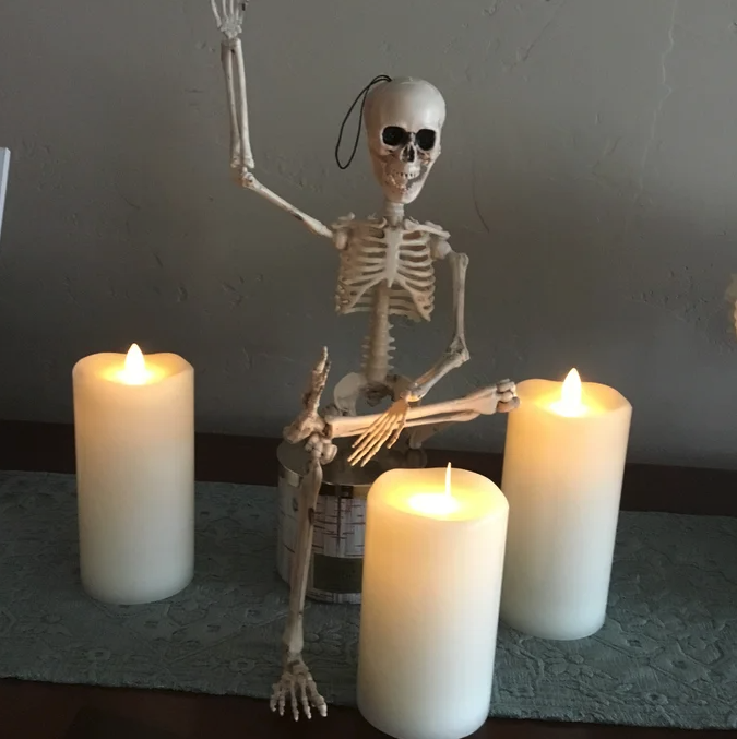 reviewer's skeleton sitting next to candles and waving