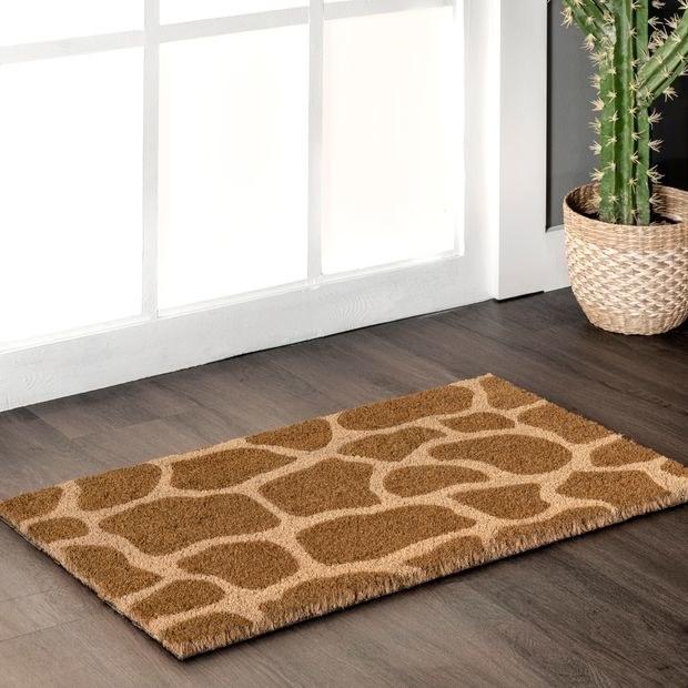 the giraffe print doormat in front of a door