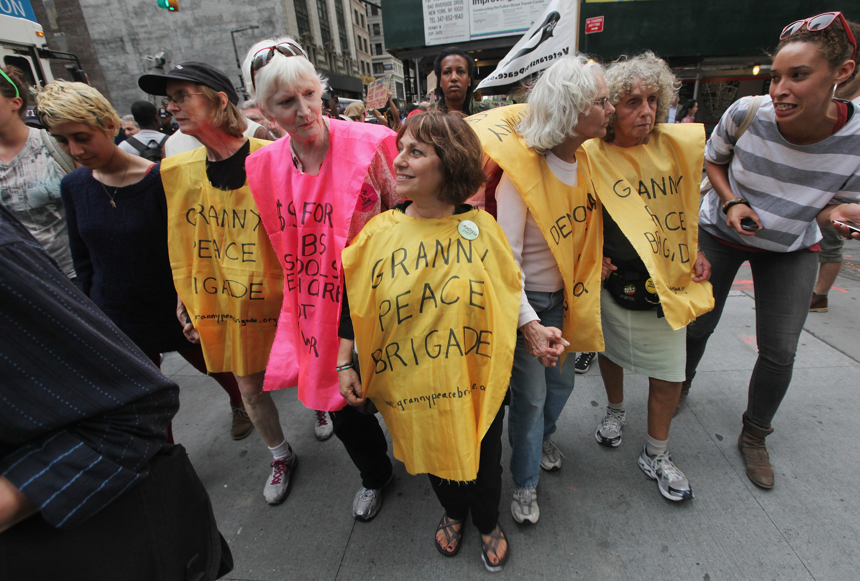 """A group of women wearing outfits that read """"Granny Peace Brigade"""" take part in Occupy Wall Street"""