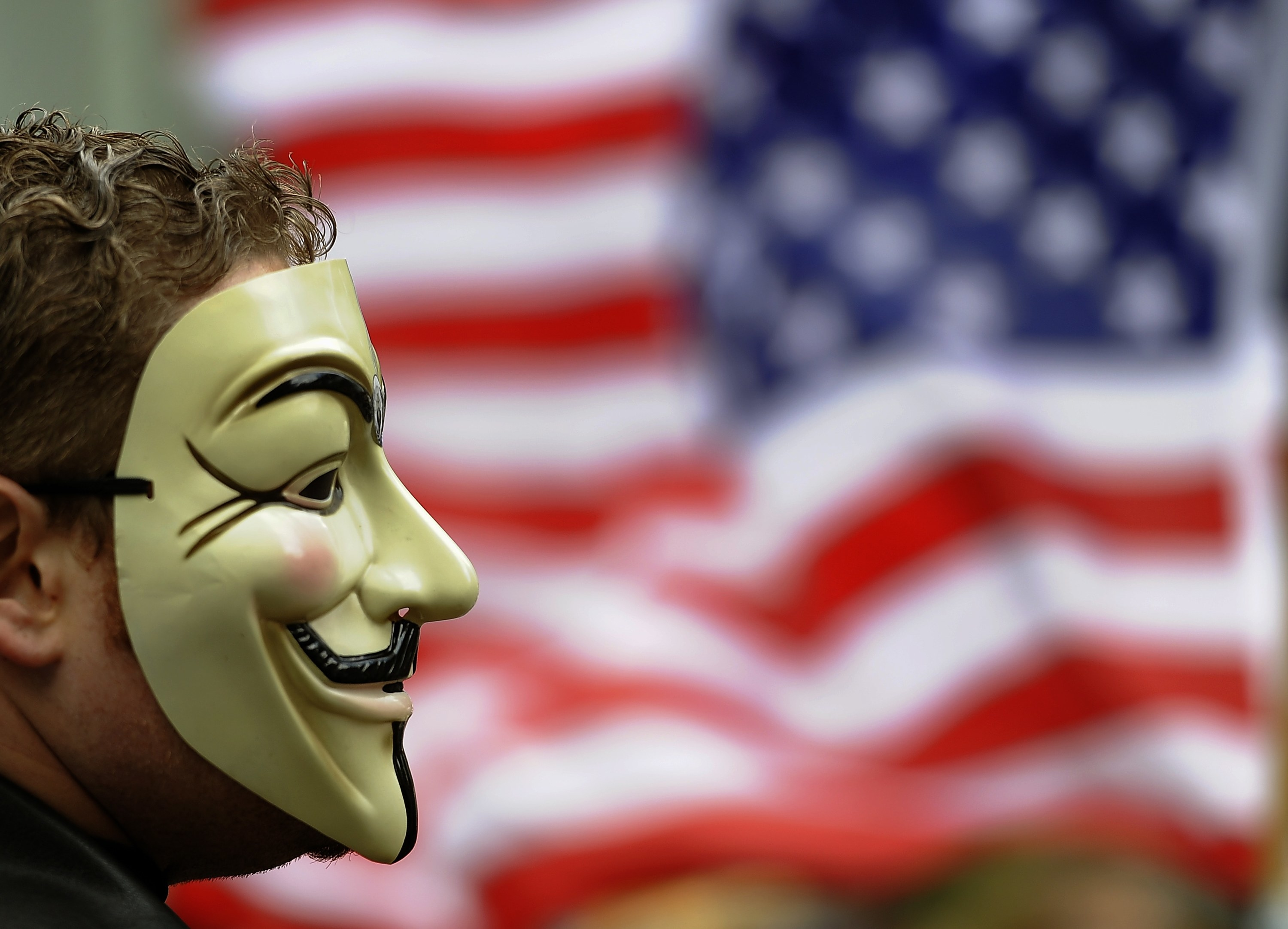 A masked protester in front of a flag during Occupy Wall Street