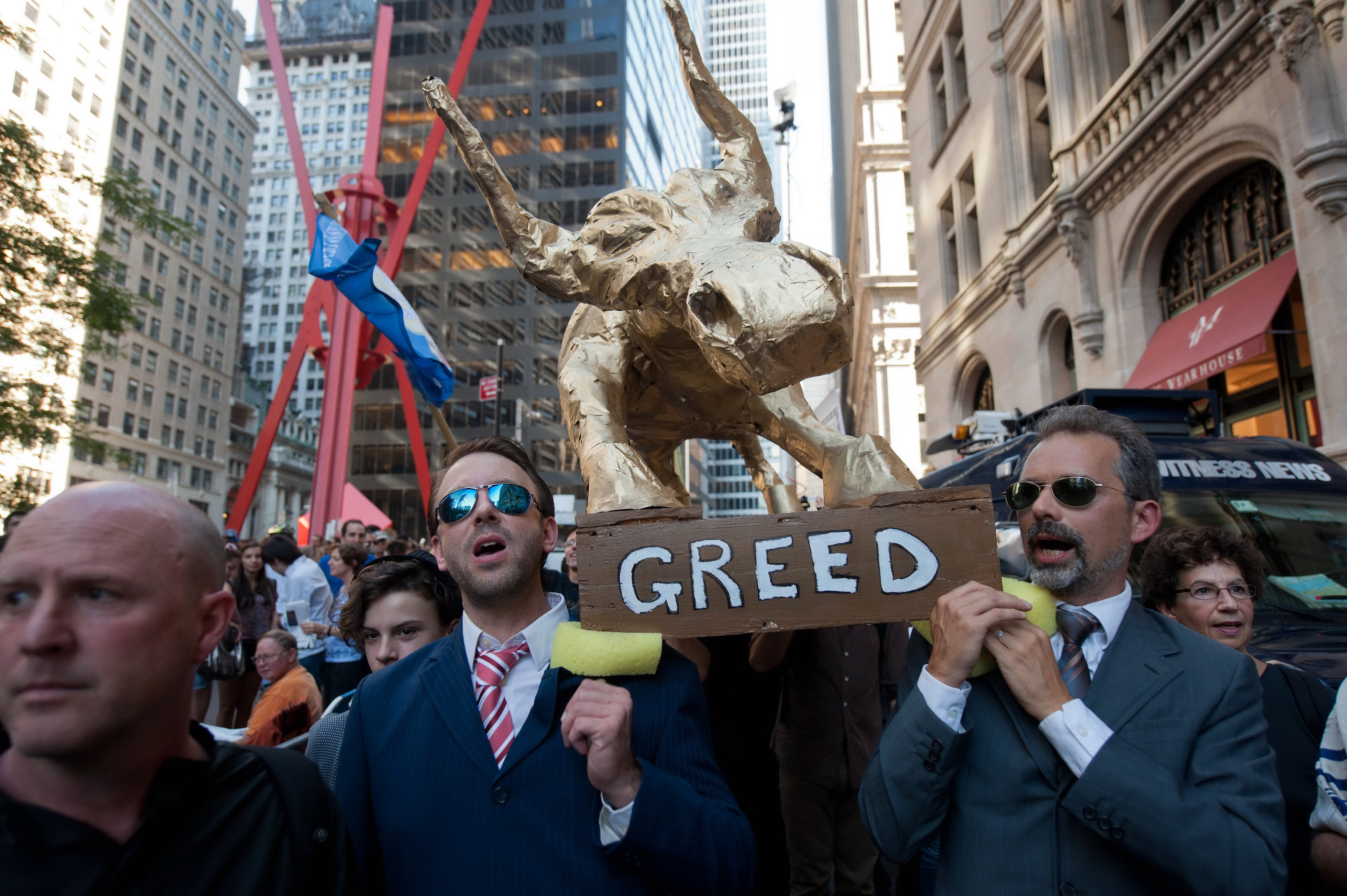 Two men in suits hold a sign that reads 'greed' in downtown New York