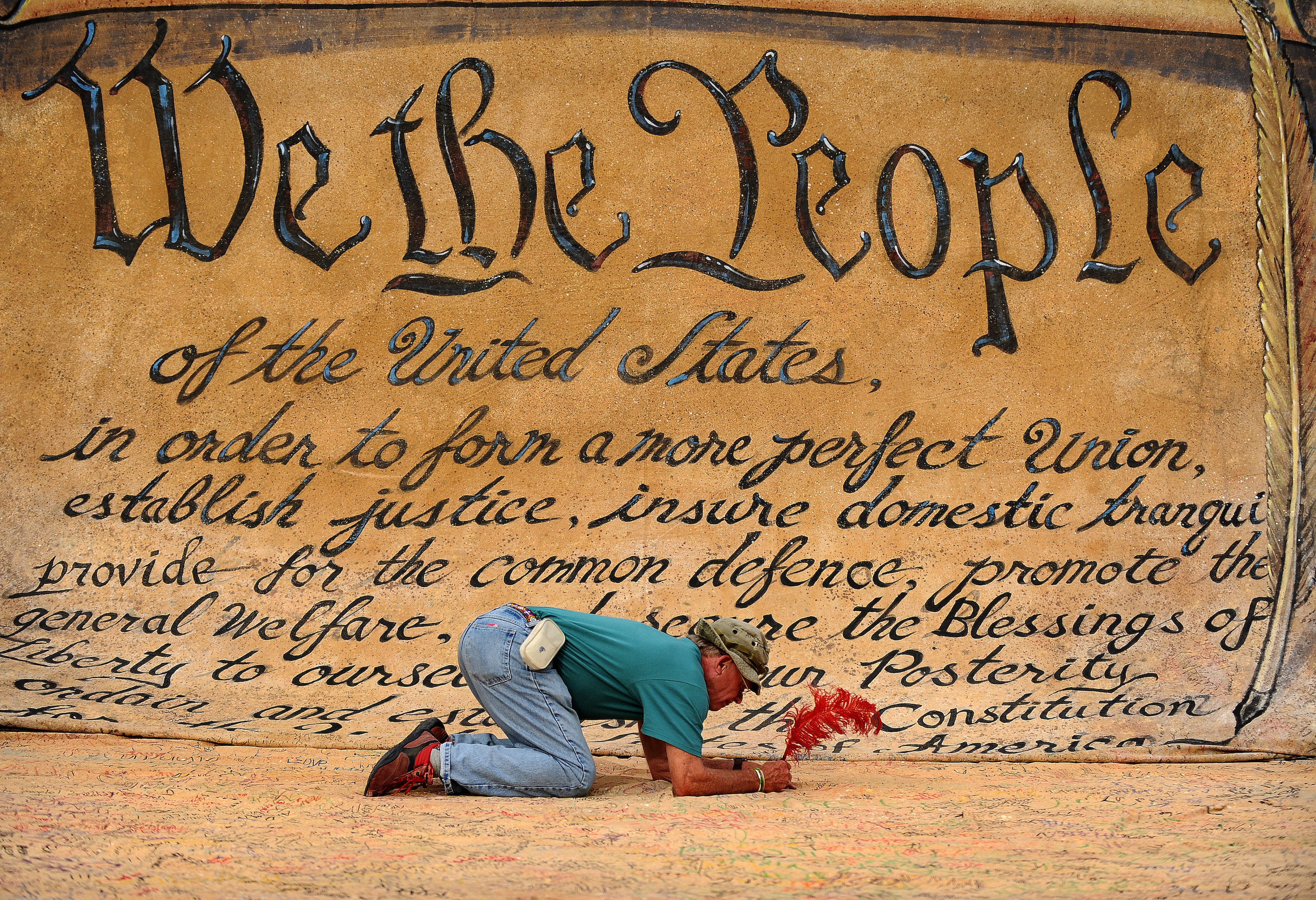 A man signs a large drawing of the Constitution at a protest in Washington, DC