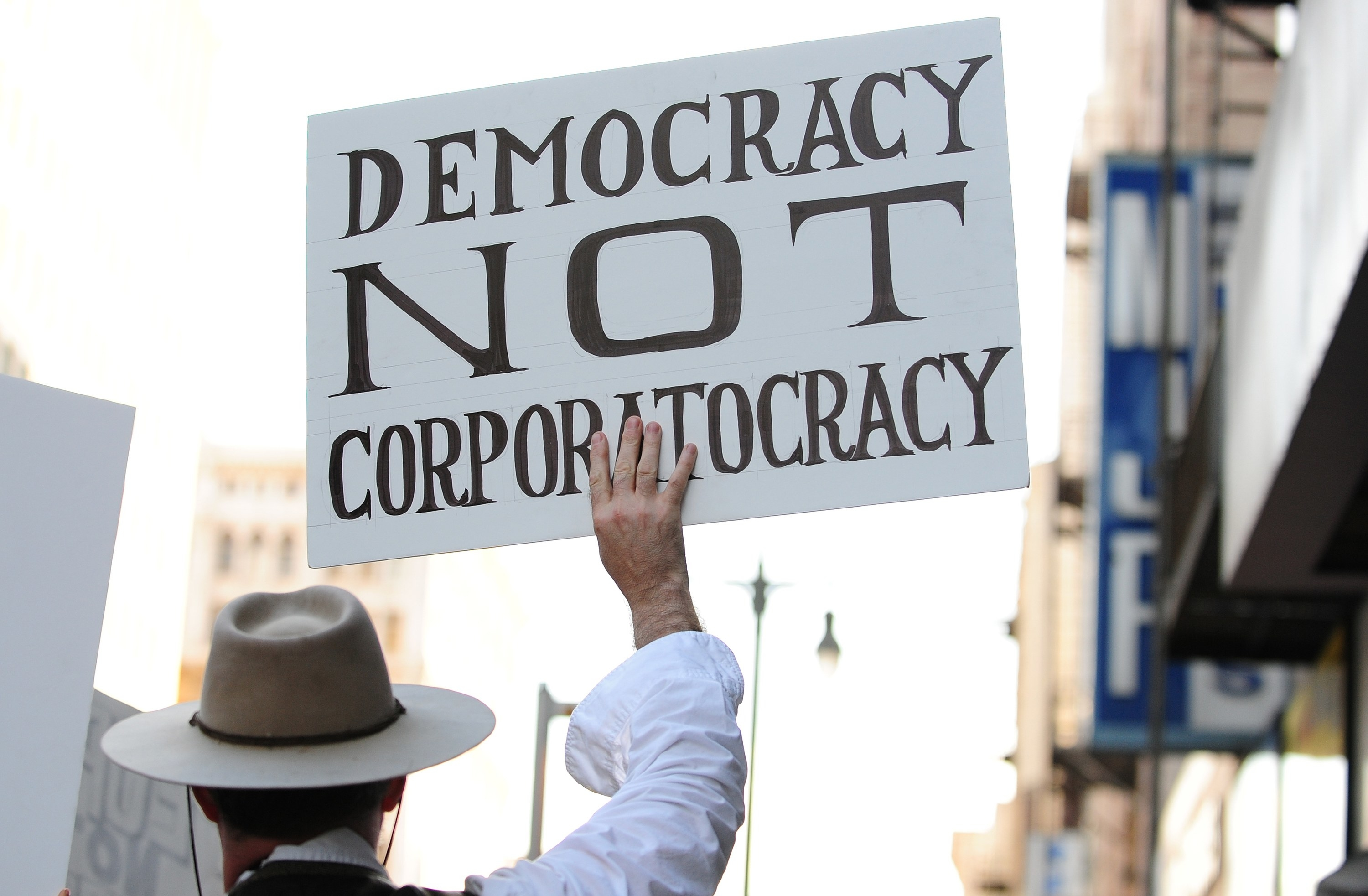 """The sign that reads """"Democracy Not Corporatocracy"""""""