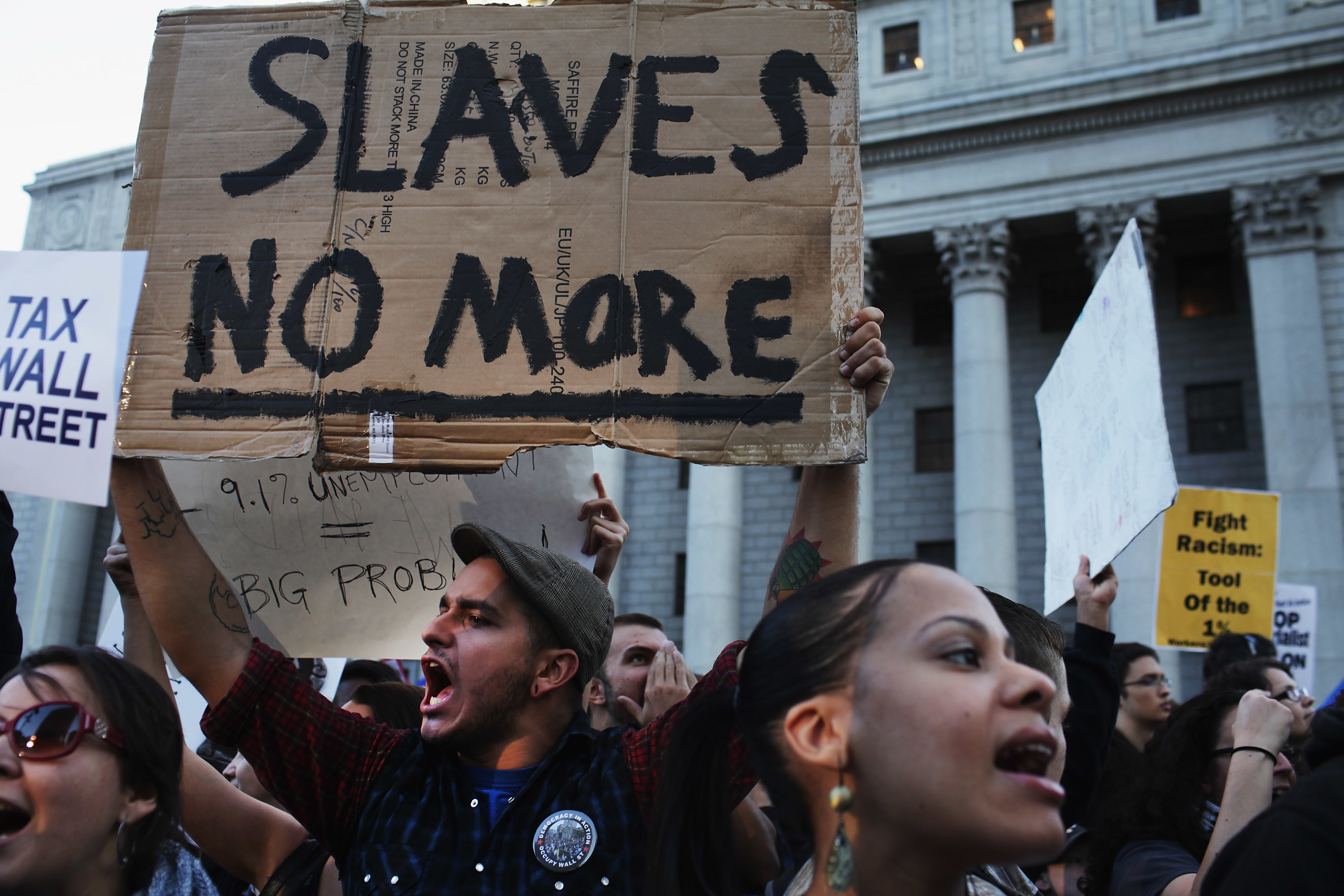 """A man holds a sign that reads """"slaves no more"""" at an Occupy Wall Street march"""